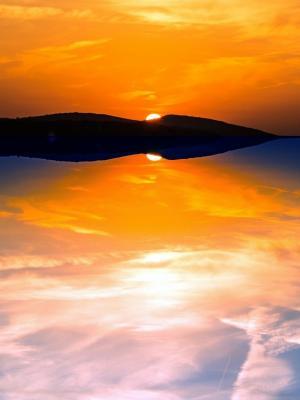 橙色的天空反映在平静的海上移动壁纸